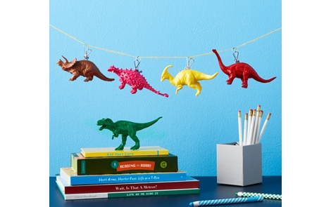 Five painted dinosaurs on a stack of books